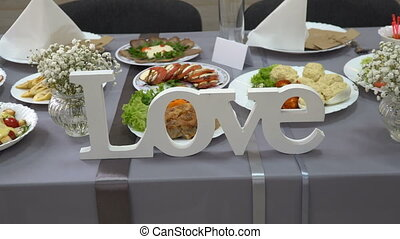 Wooden word Love on the wedding table of the bride and groom