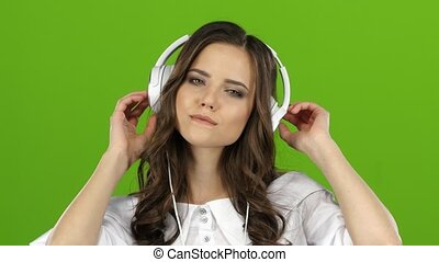 Girl enjoys music through headphones and sing along. Green...