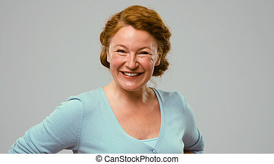 Mid aged positively smiling actress. Red-haired mid aged...