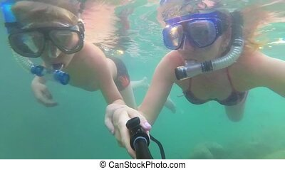 Child and girl bathe in the sea with fish. Scuba Diving in...