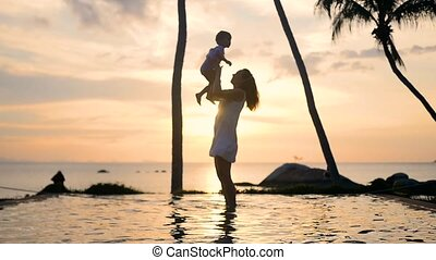 Girl with child walking and playing on the beach during sunset. family leisure