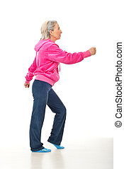 Senior woman workout in a pink-gray suit over white...