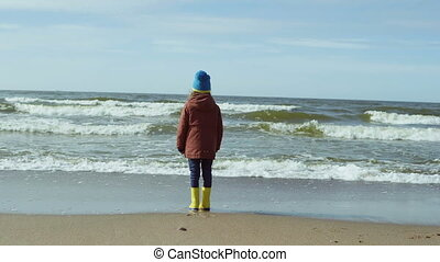 Lonely little girl in bright yellow rubber boots standing on...