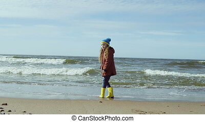 Cute little girl in bright yellow rubber boot at shore of...
