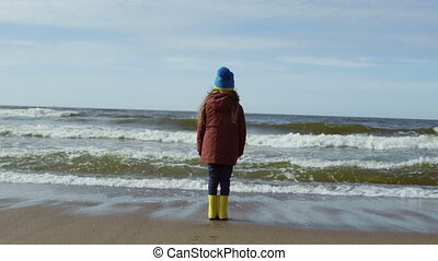 Happy child standing on shore of the sea and looking into...