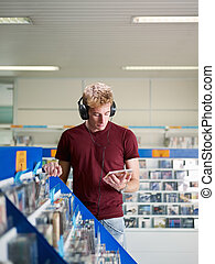 guy listening music in cd store - caucasian man with...