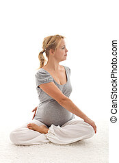 Beautiful pregnant woman doing exercises sitting on the...