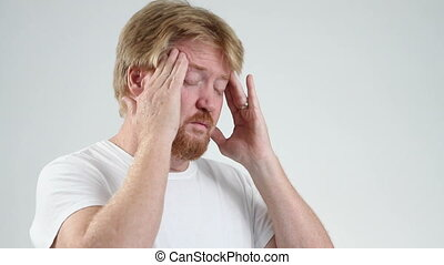 Man With Migraine - Man with a migraine headache rubs his...