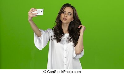 Girl of with a smartphone in her hands makes selfie. Green...