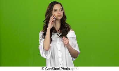 Brunette girl swears on the phone and screams. Green screen...