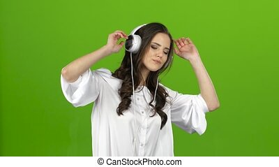 Brunette listens through the headphones with energetic music...