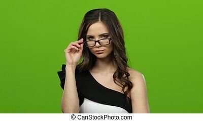 Girl with glasses flirts, bites her lip, she is sexy and tender. Green screen