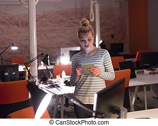 woman working on digital tablet in night office - young...