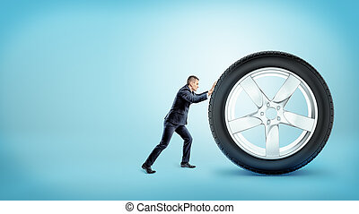 A small businessman pushing up at a huge new car tire on...