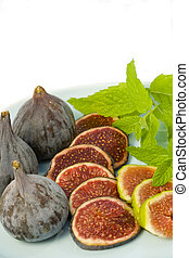 Black and green figs with fresh mint leaves vertical -...