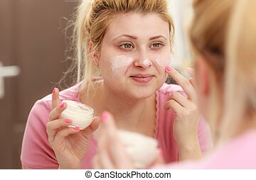 Woman applying face cream with her finger - Moisturizing...