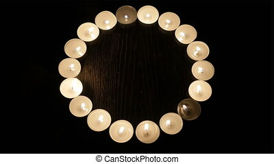 Burning candles are laid out in the shape of a circle.