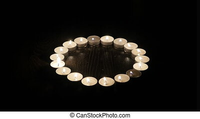 Burning candles are laid out in the shape of a circle. 4k...