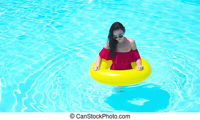 Beautiful young woman relaxing in swimming pool. Girl in...