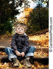 Sad little boy in autumn scene