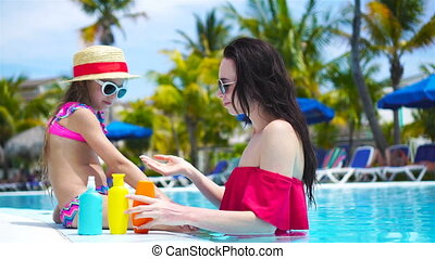 Young mother applying sun cream to kid nose in swimming pool. The concept of protection from ultraviolet radiation