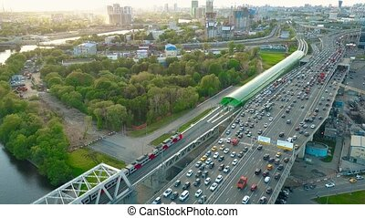 Aerial shot of heavy traffic jam and moving commuter trains...