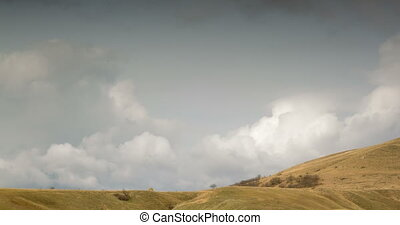 Cloudy sky above the hilly valley. timelapse