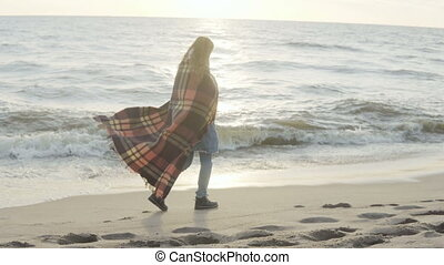 Lonely woman walking on the sandy beach with plaid. Young...