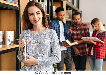 Happy woman student standing in library holding notebook -...