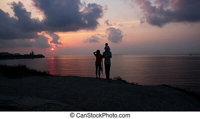 A family with a small child admiring the sea sunset on the...