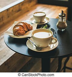Coffee latte, cappuccino and croissant on table , square...