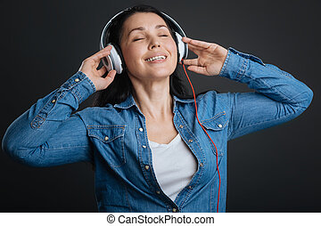 Inspired captivated woman loving the sound - Musical...