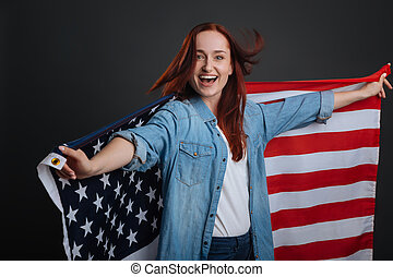 Enthusiastic happy woman dancing with national flag
