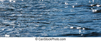 Water with bokeh background. Water surface with waves glittering in the sun. Banner for website