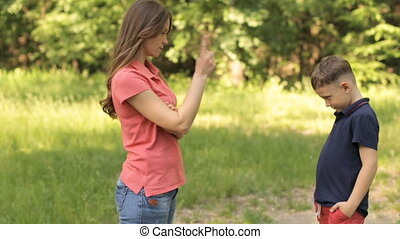 Mom scolds her son in the park - Mom scolds his little son...