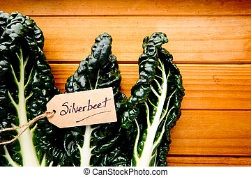 Fresh Silver beet on wooden background - with label