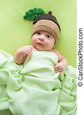 Baby with a knitted hat on back. Newborn boy lying on a bed in the cap