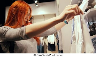 Woman chooses dress in a women's clothing store