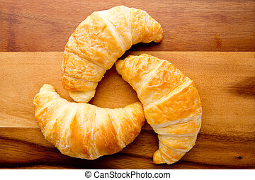 Croissants on wooden cutting board
