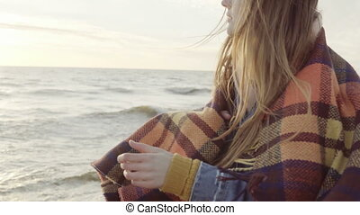 Attractive brunette woman standing on the shore of sea and dreaming. Young female enjoying the beach, waves in cold day.