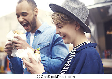 Cheerful couple having tasty hamburgers