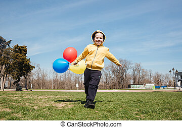 Smiling little children boy walking outdoors in park with balloons