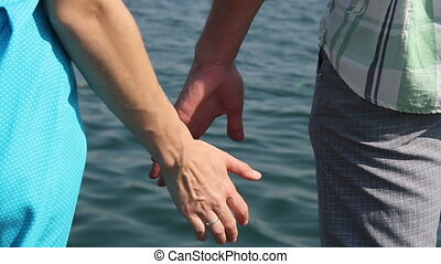 Woman and man, join hands against the sea - Woman in blue...