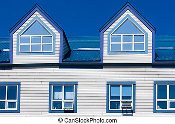 Wooden frame house blue metal roof dormer windows