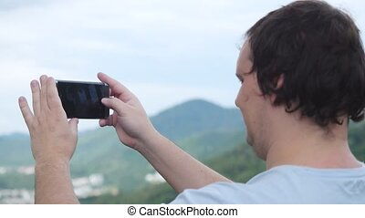 Man Standing on a Mountain Shoots on a Mobile Phone Panorama...