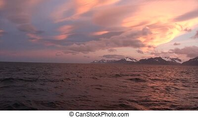 Sunset and snowy mountains on coastline of Falkland Islands Antarctica.