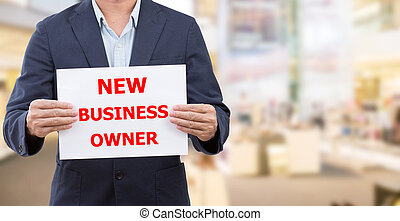 Man holding white board with new business owner message on...
