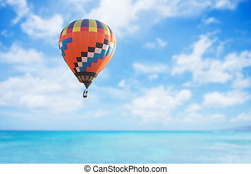 Colorful hot air balloon over blue sea