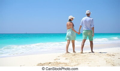Young couple on white beach during summer vacation. Happy lovers enjoy their honeymoon.
