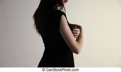 A young woman nestles her fingers over her shoulder, hides...